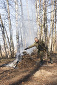 Man throw leaves and spray into bonfire — Stock Photo