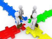Four businessmen meet on puzzle crossroad — Stock Photo