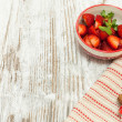 Fresh strawberries in bowl over wooden background. — Stock Photo