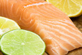 Fresh salmon steak with lemon and lime slice — Stock Photo