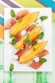 Melon slices with prosciutto and mozzarella — Stock Photo
