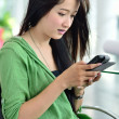 Beautiful young womusing mobile phone — Stock Photo #14985091