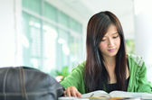 Beautiful asian girl is reading and smile — Stock Photo