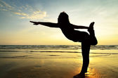 Silhouette Asian woman practicing yoga at the beach — Stock Photo