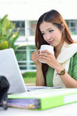 Asian women student smiling with coffee cup — Stock Photo