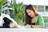 Beautiful young asian student is reading and writing — Stock Photo