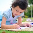 Going back to school,Girl drawing and painting over green grass  — Stock Photo