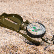 Royalty-Free Stock Photo: Compass showing a direction, lies on sea sand
