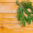 Foto de Stock  : Christmas fir tree on the wooden board to be used as backgroud or postcard