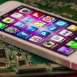 IPhone 5 Apps screen on a mainboard surface - Stock Photo
