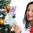 Beautiful woman with money and Christmas tree — Stock Photo