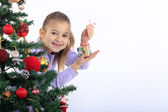 Little girl with a gift and Christmas tree — Stock Photo