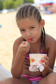 Little girl eating ice cream on the beach — Stock Photo