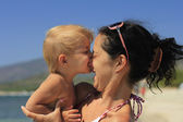 Baby biting her mother's nose — Stock Photo