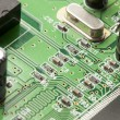 Green Electrical Circuit Board with microchips and transistors - Photo