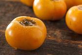 Organische oranje persimmon vruchten — Stockfoto