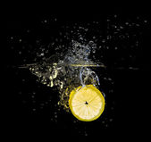 Fresh lemon slice splash on black — Stock Photo