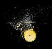 Fresh lemon slice splash on black — Stock Photo