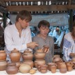 Постер, плакат: Two guys and a girl selling pottery
