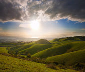 Spring sunset over green hills — Stock Photo