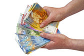 Swiss francs banknotes hold in female hand — Stock Photo