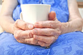 Senior hand hold a cup of tea — Stock Photo