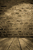 Old brick wall with wooden floor — Stock Photo