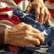 Hands on an American flag - Stock Photo