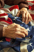 Hands on American flag — Stock Photo