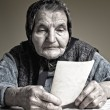 Elderly woman with old photos — Stock Photo