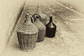 Woven wicker wine bottles. — Stock Photo