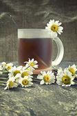 Cup of tea and chamomile flowers — Stock Photo