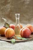 Fresh and tasty apricot fruit and apricot brandy on a plate. — Stock Photo