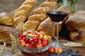 Still life with bread, cherry, and wine on wooden table. — Stock Photo