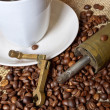 Coffee beans with coffee grinder and cup of coffee — Stock Photo