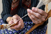 Old hands spinning wool. — Stock Photo