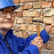 Elderly woman with a hammer and chisel. — Stock Photo