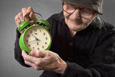 Elderly woman holding an alarm clock. — Stock Photo
