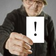 Elderly woman holding card with printed exclamation mark — Stock Photo #42015531