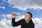 Young caucasian girl starts paper plane in blue sky — Stock Photo