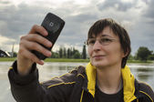 Woman in nature taking selfie using smart phone. — Stock Photo