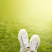 A pair of white trainers in the grass in the sunshine — Stock Photo