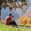 Stock Photo: Man taking photos under autumn tree