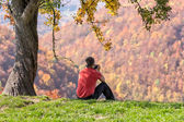 Man taking photos under autumn tree — Stock Photo