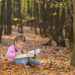 Little girl reading book in autumn forest — Stock Photo
