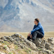 Man relaxing on top of mountain — Stock Photo