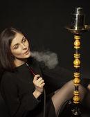 Glamor girl smokes a hookah — Stock Photo