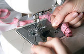 Hand threading needle into sewing needle. For concepts such as fashion and design, work and industrial. — Stock Photo
