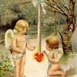 A vintage Valentine card with two cherubs warming up next to a h — Stock Photo