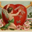 Stock Photo: A vintage Valentines card with a cherub patching up a broken hea